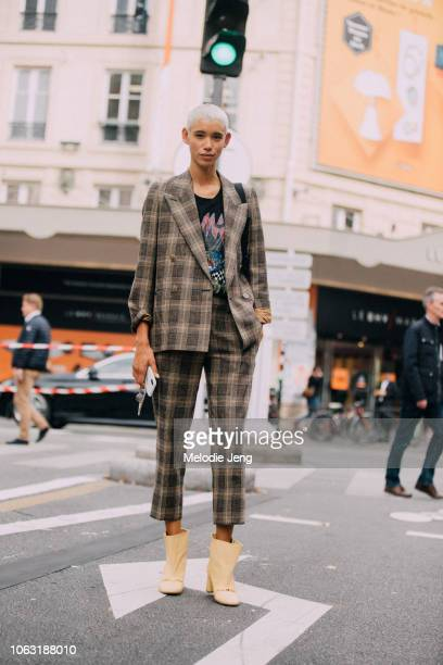 Model Dilone wears a matching plaid jacket and pants yellow open boots Imari wears a black sport jumpsuit skinny black sunglasses and black boots...