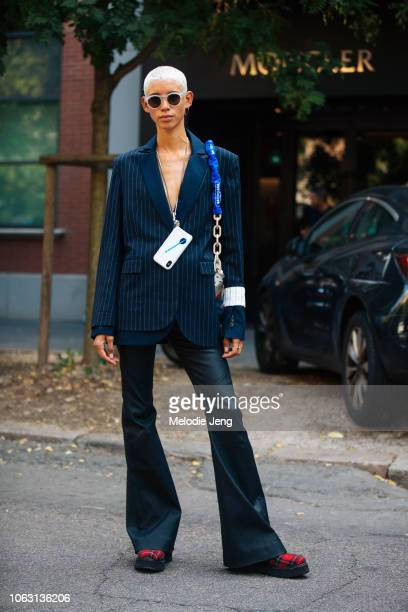 Model Dilone wears white sunglasses a phone around her neck blue striped blazer Balenciaga bag black flare leather pants during Milan Fashion Week...