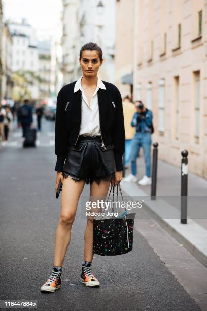 Model Dipti Sharma wears a black jacket, white blouse, black leather shorts, black flame Converse sneakers, and a black paint-splattered leather tote...
