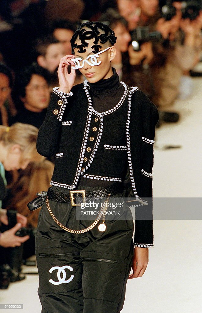 A model displays 10 March 1994 in Paris a black jacket and a black waistcoat embroidered with a white cotton, and trousers styled commando designed by Karl Lagerfeld for 1994/95 Autumn/Winter ready-to-wear collection of Chanel.