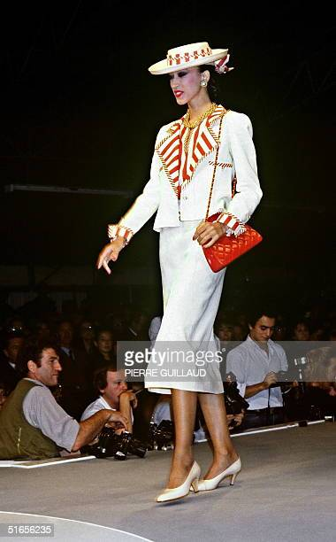A model displays 18 October 1983 in Paris a white suit made in demin with border application striped red and yellow topped with a matched hat for...