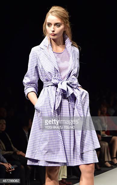 A model displays a creation of Japanese designers Yuki Torii during her 2015 spring and summer collection in Tokyo on October 16 2014 as a part of...