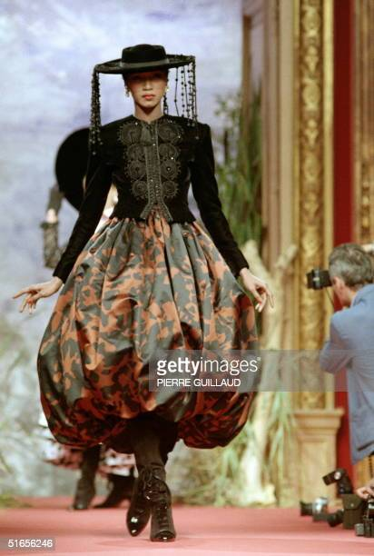 A model displays a styled Spanish ensemble black jacket embroidered over a balloondress and Castilian hat for Christian Lacroix 1987/88 Fall/Winter...