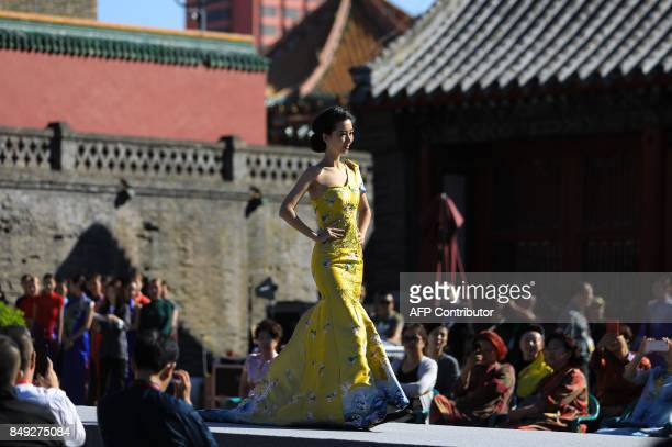 A model displays an updated version of the cheongsam also known as a qipao during the First Shenyang International Cheongsam Cultural Festival at...