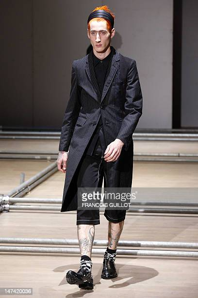 A model displays creations by Japanese designer Rei Kawakubo for the Comme des Garcons fashion house during the men's springsummer 2013 fashion...