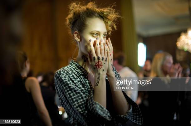 A model displays her temporary tattoos ahead of the Vivienne Westwood show at London Fashion Week in central London on February 19 2012 London...