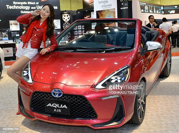 A model displays Japanese auto giant Toyota Motor's prototype model of a convertible hybrid vehicle Aqua Air equipped with a 15litter...