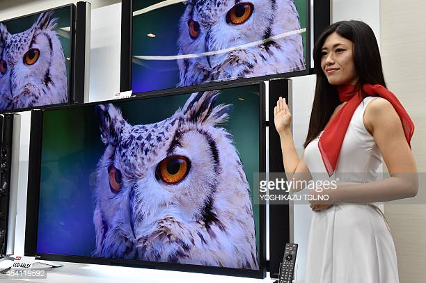A model displays Japanese electric maker Mitsubishi Electric's new 4K television Real LS1 which has 65inch and 58inch sized LCD display in Tokyo on...
