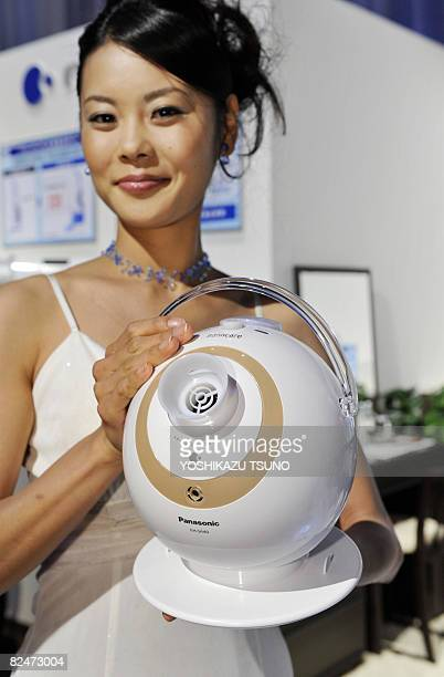 A model displays Japanese electronics giant Matsushita Electric Industrial's new beauty product the Nanocare humidifier which provides moisture to...