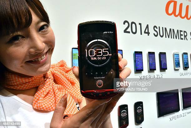 A model displays Japanese mobile communication giant KDDI's new heavyduty smartphone 'Torque' which complies with military standard 'MILSTD810G' of...