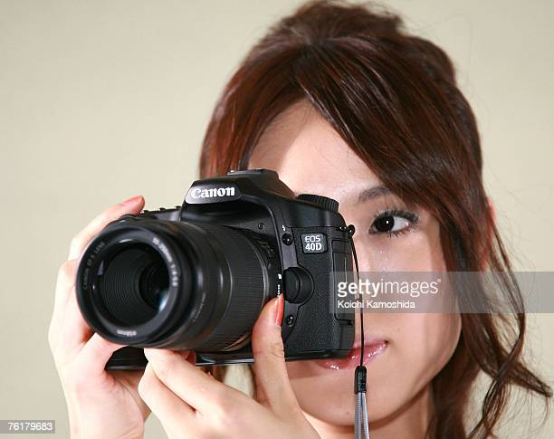 Model displays the new Canon EOS 40D digital SLR camera during a press preview on August 20, 2007 in Tokyo, Japan. The new camera features a...