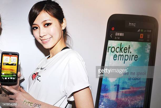 A model displays the 'One' series new models of Taiwan's smartphone maker HTC during a press conference in Taipei on March 26 2012 The new series...