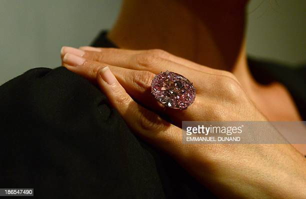 A model displays 'The Pink Star' a 5960carat oval cut pink diamond during a press preview at Sotheby's in New York November 1 2013 The Pink Star is...