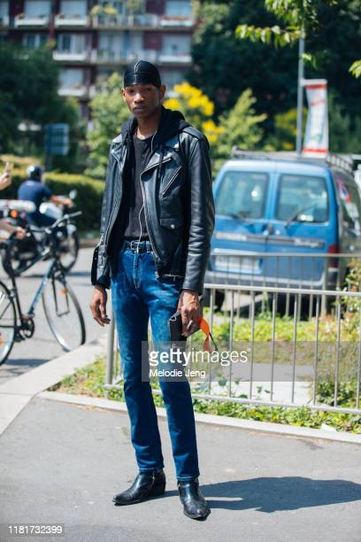 Model Dominic Augustin wears a black durag, black leather jacket, blue jeans, and black boots after the Pal Zileri show during the Milan Men's...
