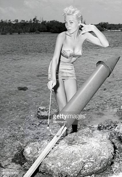 Model Doreen Evans strikes a kittenish pose and blocks an ear as she lights the fuse of a giant skyrocket on the beach at Miami a few days before the...