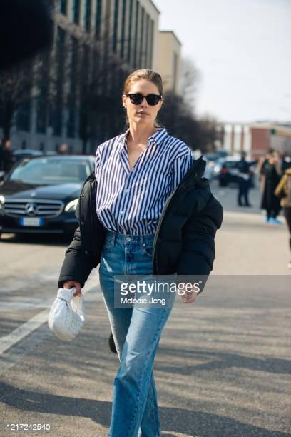 Model Doutzen Kroes wears a black bomber jacket off her shoulders, black sunglasses, a blue striped shirt, blue jeans, and a white Bottega Veneta...