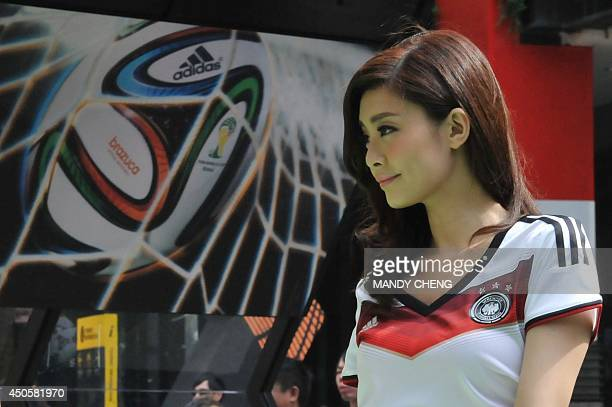 A model dressed as a footballer poses next to a post of a Brazuca ball the official soccer ball of the 2014 World Cup during a press conference in...