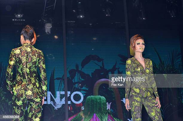 A model dressed by Kenzo and a model with a painted body walk the runway during the show 'The Art Of Illusion' at Palais De Tokyo on September 24...