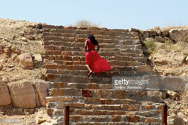 CONTENT] Model dressed in red climbs the stairs of telegraph island in the fjords of Musandam