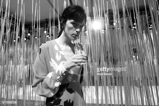 A model drinks Evian water during the Tanya Taylor presentation in Gallery II during IMG NYFW The Shows at Spring Studios on February 11 2018 in New...