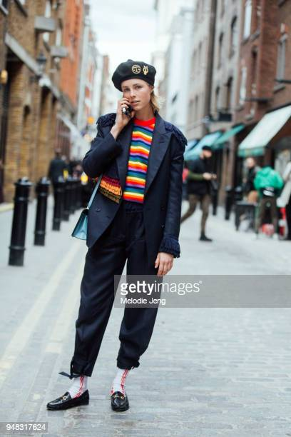 Model Edie Campbell talks on the phone and wears an Itchy Scratchy Patchy Lyre Scales Tam o'Shanter Black wool tam hat with military goldwork patches...