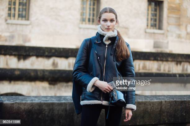 Model Elien Swalens holds an iPhone and wears a black shearling bomber jacket and Calvin Klein bag after the Valentino show on March 04 2018 in Paris...