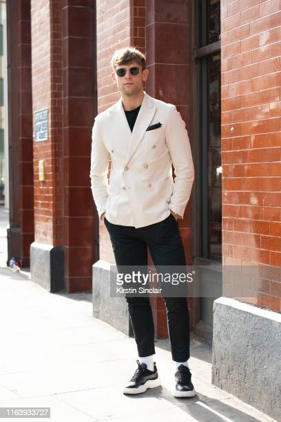Model Elliott Reeder wears Ray Ban sunglasses Circolo 1901 jacket and trousers Valentino trainers during London Fashion Week Men's June 2019 on June...