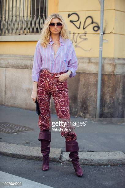 Model Elsa Hosk wears shaded sunglasses a pink and purple stripe shirt red Etro paisley print pants and purple suede boots at the Etro show during...