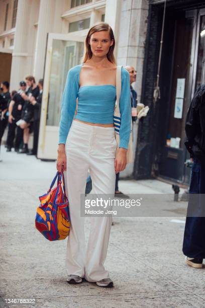 Model Elsemarie Riis wears a blue knit top, white pants, and colorful print shopping bag after the Tory Burch show on September 12, 2021 in New York...