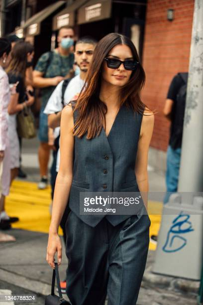 Model Emily Ratajkowski wears black sunglasses, matching gray waistcoat/vest and pants after the Tory Burch show on September 12, 2021 in New York...