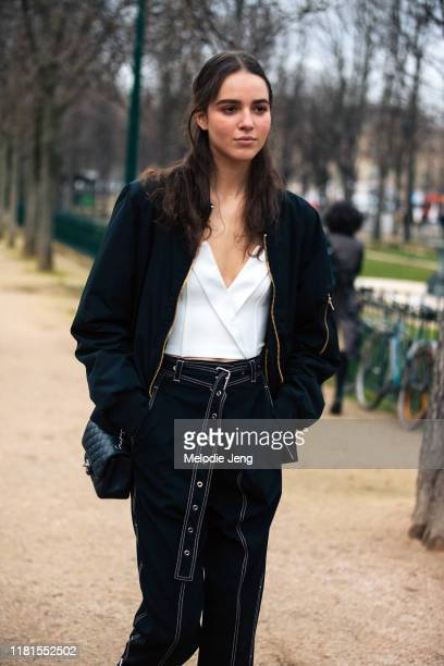 Model Emm Arruda wears a black blazer white top and blue pants after the Chanel show during Paris Fashion Week Fall/Winter 2019 on March 05 2019 in...