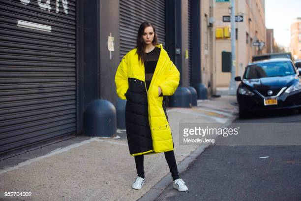 Model Emm Arruda wears a black yellow long down puffer parka with a black sheer top and white sneakers February 12 2018 in New York City