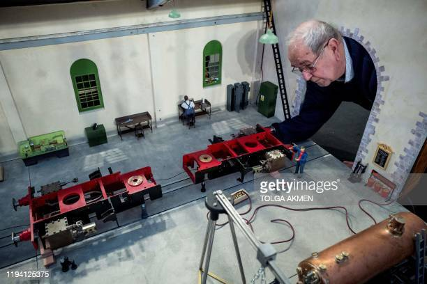 Model engineer puts the final touches to a model train depot during a photocall at the London Model Engineering Exhibition at Alexandra Palace in...
