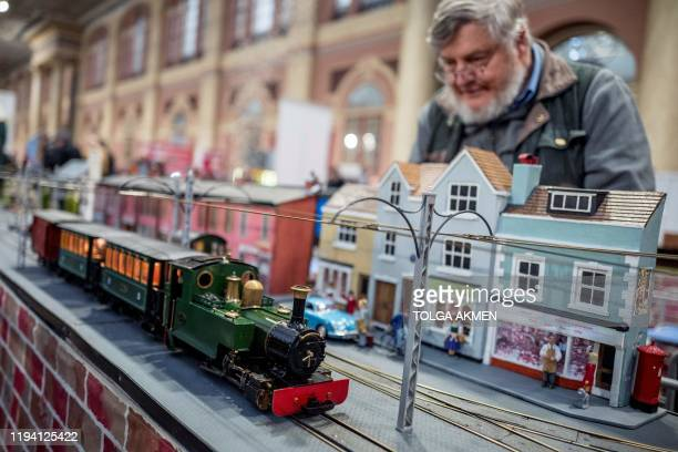 Model engineers from The Buckinghamshire Garden Railway Society operate a miniature steam train during a photocall at the London Model Engineering...