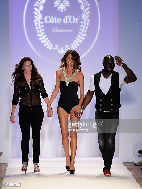Model escorts designers Stephanie Theis Fajardo and Kevin Fitzpatrick on the runway for the Cote D'Or Swimwear collection during the Anna Kosturova,...