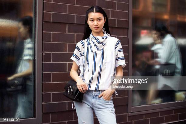 Model Estelle Chen in a blue and white stripe shirt and black paperclip bag after the 31 Phillip Lim show during New York Fashion Week Spring/Summer...