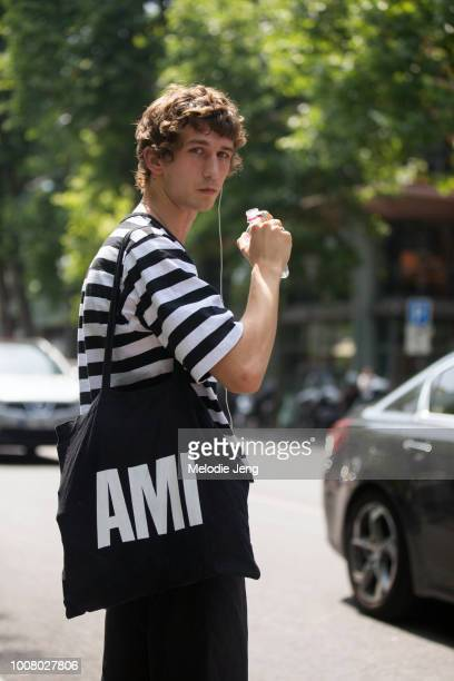 Model Etienne de Testa drinks water and wears a black and white striped shirt after the AMI Alexandre Mattiussi show during Paris Fashion Week Men's...