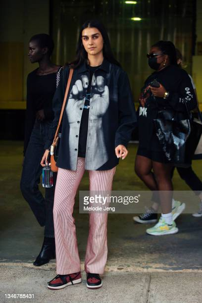 Model Eugenia Dubinova wears a blakc shirt with a hand, pink stripe pants, red and black Nike sneakers, and holds a Fiji water on September 12, 2021...