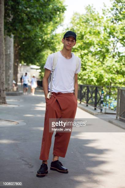 Model Evan in a black cap white tshirt orange pants and black shoes after the AMI Alexandre Mattiussi show during Paris Fashion Week Men's...