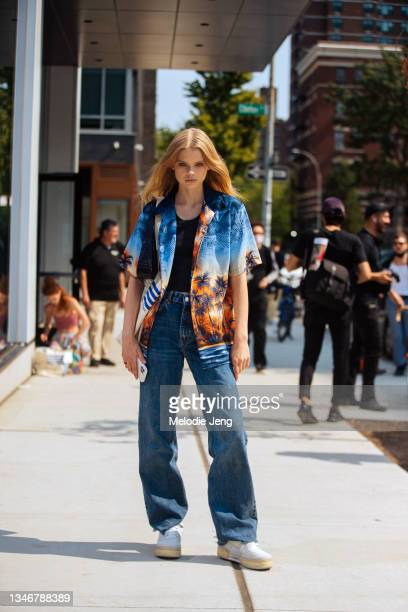 Model Evie Harris wears a blue and orange palm street print shirt, black top, blue jeans, and white sneakers after the Khaite show on September 12,...