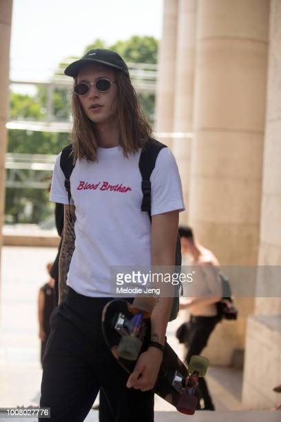 A model exits the Rick Owens show in a Wood Wood cap Blood Brother tshirt and his skateboard at Palais de Tokyo during Paris Fashion Week Men's...
