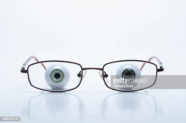 Model eyeballs behind spectacles with myopic (negative) lenses