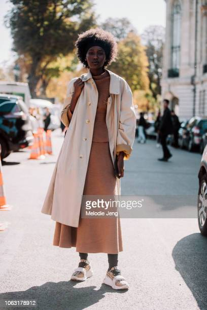 Model Fatdwa at Mademoiselle Agency wears a tan jacket caramel dress and yellow Burberry print sandals after the Jour/ne show during Paris Fashion...