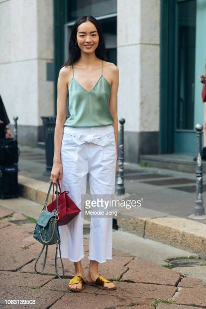 Model Fei Fei Sun wears a green silk tank top, white pants, blue Chloe bag, and yellow velvet sandals after the Ferragamo show during Milan Fashion...