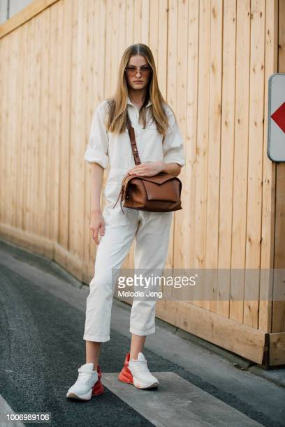 Model Felice Nova Noordhoff wears Dior sunglasses a white jumpsuit brown Givenchy bag and red and white Nike sneakers during Couture Fall/Winter 2018...