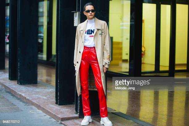 Model Fernanda Oliveira wears a tan trenchcoat with illustrations a Fendi Roma white roll neck bright red leather pants white boots and futuristic...
