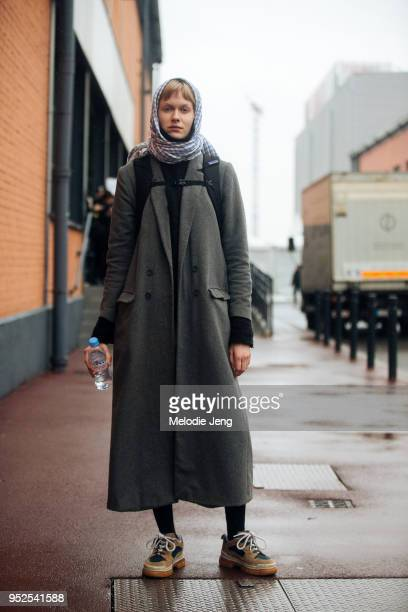 Model Fie Ljungmann wears a patterned scarf around her head a long great coat and brown sneakers after the Balenciaga show on March 04 2018 in Paris...
