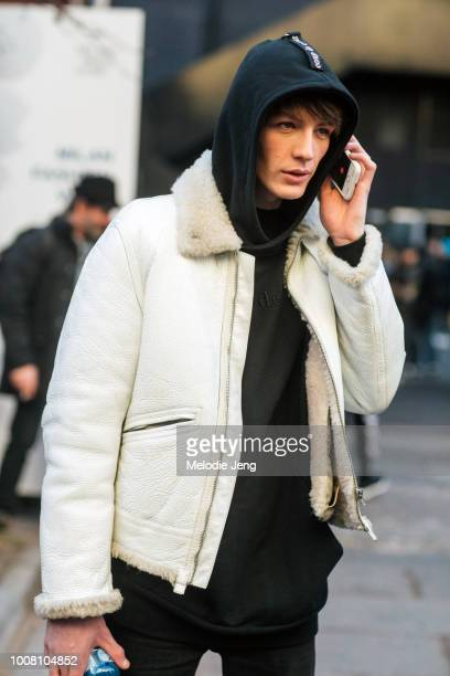 Model Finnlay Davis talks on the phone and wears a coup de coeur black hoodie and white shearling leather bomber jacket after MSGM during Milan Men's...