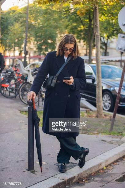 Model Florence checks their phone and wears sunglasses, a long blue peacoat, black cross-body Bottega Veneta Cassette bag, black dress pants, black...