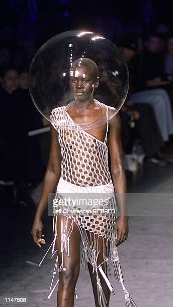 A model for designer Julien Macdonald wears a mesh top and a plastic bubble on her head November 5 during a showing of the designer's Spring 1999...